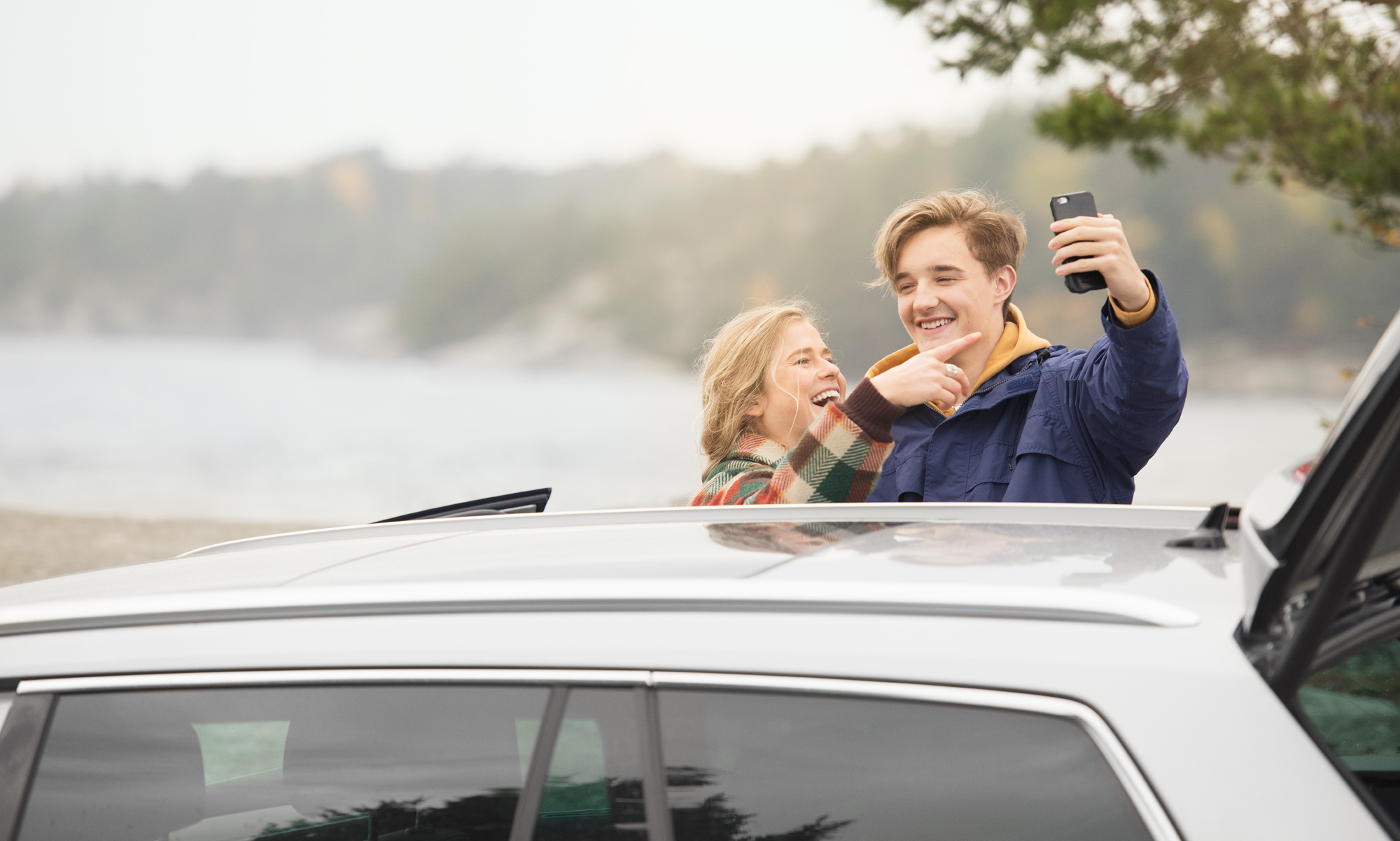 Young couple taking a selfie outside the car by the sea